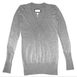 A gray long sleeved v-neck sweater.